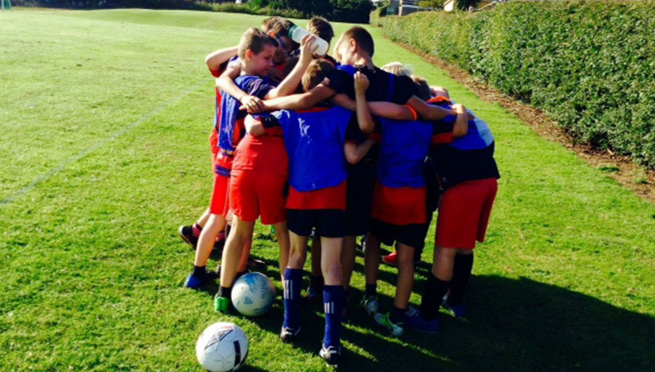 Laughton school children in a huddle playing sports